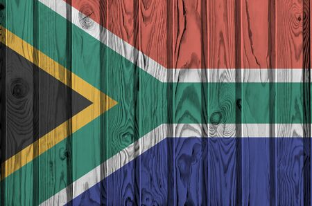 South Africa flag depicted in bright paint colors on old wooden wall close up. Textured banner on rough background
