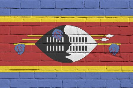 Swaziland flag depicted in paint colors on old brick wall close up. Textured banner on big brick wall masonry background Stock fotó