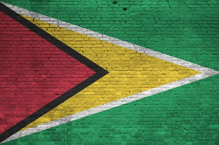 Guyana flag depicted in paint colors on old brick wall close up. Textured banner on big brick wall masonry background