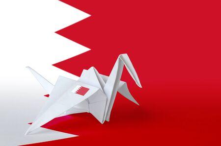 Bahrain flag depicted on paper origami crane wing. Oriental handmade arts concept Reklamní fotografie