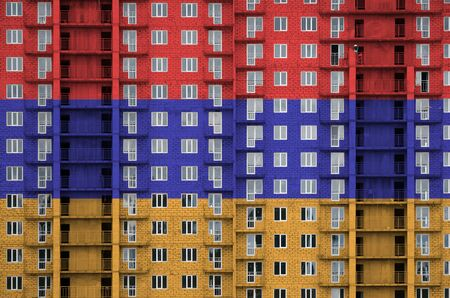 Armenia flag depicted in paint colors on multi-storey residental building under construction. Textured banner on big brick wall background