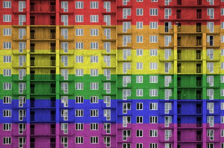 LGBT community flag depicted in paint colors on multi-storey residental building under construction. Textured banner on big brick wall background Zdjęcie Seryjne - 135365336