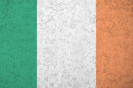 Flaga Irlandii przedstawiona w jasnych kolorach farby na starej ścianie tynku reliefowego z bliska. Teksturowany baner na szorstkim tle