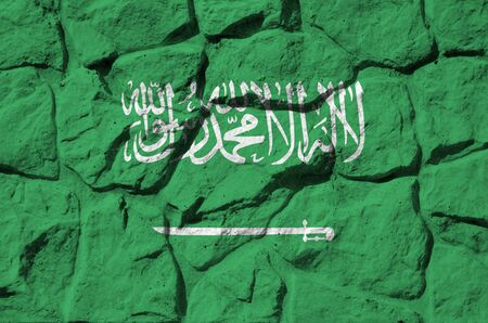 Saudi Arabia flag depicted in paint colors on old stone wall close up. Textured banner on rock wall background Stock Photo