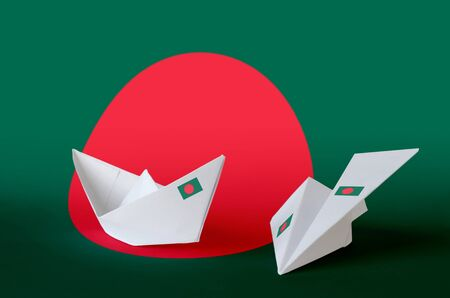Bangladesh flag depicted on paper origami airplane and boat. Oriental handmade arts concept