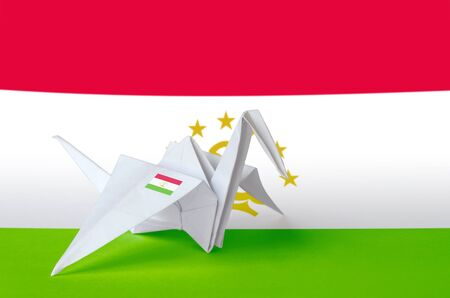 Tajikistan flag depicted on paper origami crane wing. Oriental handmade arts concept Stock fotó