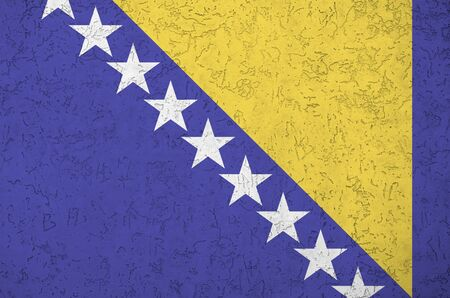 Bosnia and Herzegovina flag depicted in bright paint colors on old relief plastering wall close up. Textured banner on rough background