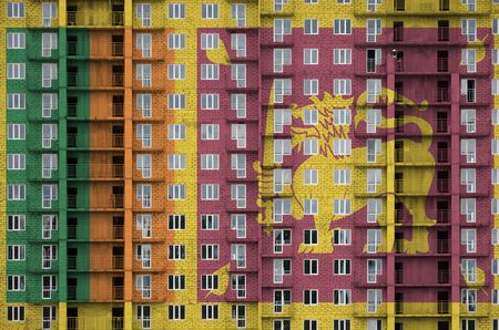 Sri Lanka flag depicted in paint colors on multi-storey residental building under construction. Textured banner on big brick wall background
