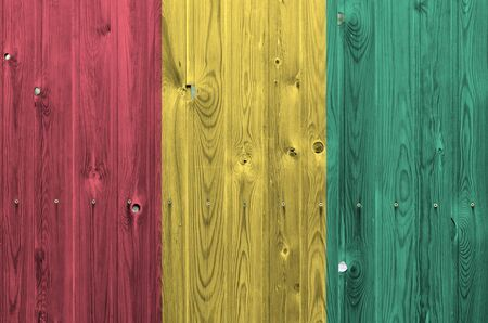 Guinea flag depicted in bright paint colors on old wooden wall close up. Textured banner on rough background Stock fotó