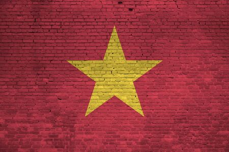 Vietnam flag depicted in paint colors on old brick wall close up. Textured banner on big brick wall masonry background