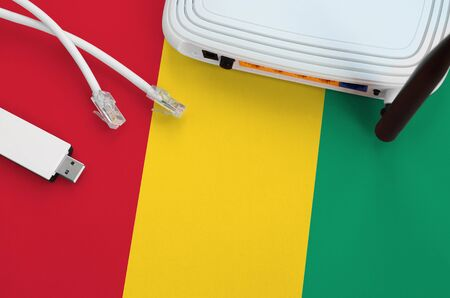 Guinea flag depicted on table with internet rj45 cable, wireless usb wifi adapter and router. Internet connection concept
