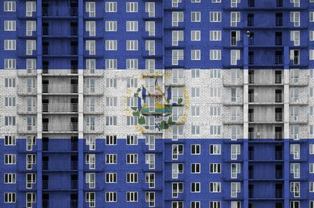 El Salvador flag depicted in paint colors on multi-storey residental building under construction. Textured banner on big brick wall background