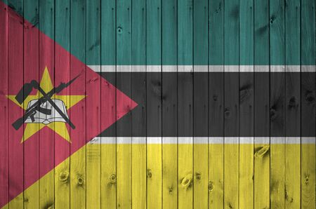 Mozambique flag depicted in bright paint colors on old wooden wall close up. Textured banner on rough background
