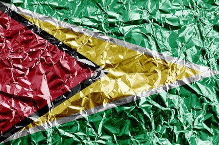 Guyana flag depicted in paint colors on shiny crumpled aluminium foil close up. Textured banner on rough background