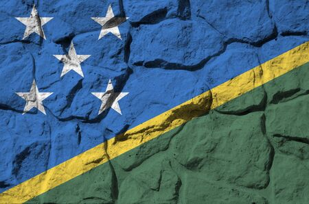 Solomon Islands flag depicted in paint colors on old stone wall close up. Textured banner on rock wall background Stockfoto