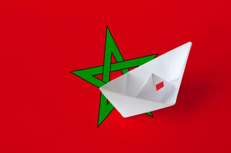Morocco flag depicted on paper origami ship closeup. Oriental handmade arts concept