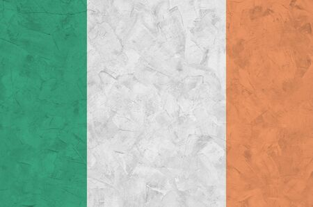 Ireland flag depicted in bright paint colors on old relief plastering wall close up. Textured banner on rough background