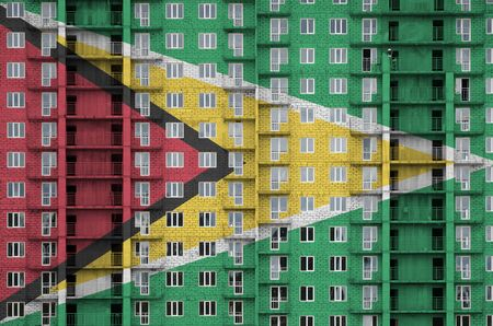 Guyana flag depicted in paint colors on multi-storey residental building under construction. Textured banner on big brick wall background Stock fotó