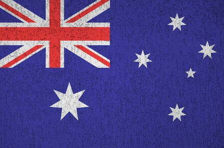 Australia flag depicted in bright paint colors on old relief plastering wall close up. Textured banner on rough background