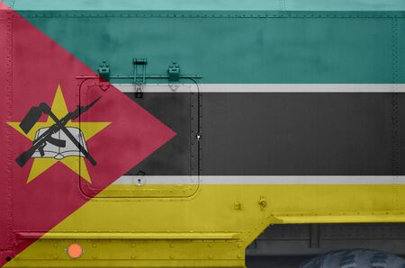 Mozambique flag depicted on side part of military armored truck close up. Army forces vehicle conceptual background
