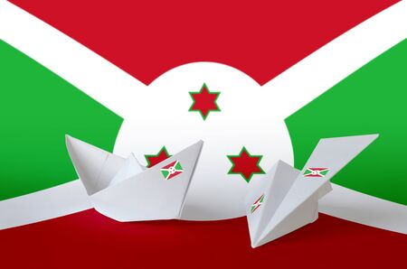 Burundi flag depicted on paper origami airplane and boat. Oriental handmade arts concept