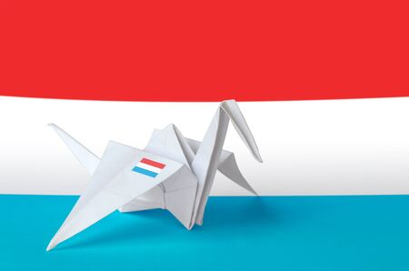 Luxembourg flag depicted on paper origami crane wing. Oriental handmade arts concept