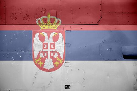 Serbia flag depicted on side part of military armored helicopter close up. Army forces aircraft conceptual background