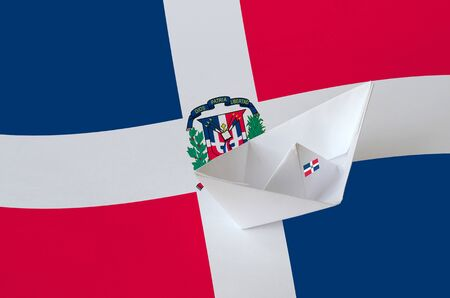 Dominican Republic flag depicted on paper origami ship closeup. Oriental handmade arts concept