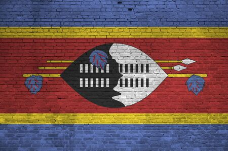 Swaziland flag depicted in paint colors on old brick wall close up. Textured banner on big brick wall masonry background