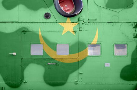 Mauritania flag depicted on side part of military armored helicopter close up. Army forces aircraft conceptual background