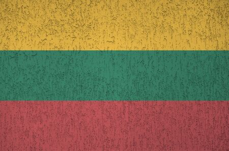 Lithuania flag depicted in bright paint colors on old relief plastering wall close up. Textured banner on rough background