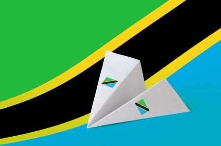 Tanzania flag depicted on paper origami airplane. Oriental handmade arts concept