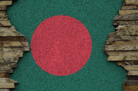 Bangladesh flag depicted in paint colors on old stone wall close up. Textured banner on rock wall background