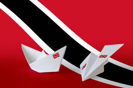Trinidad and Tobago flag depicted on paper origami airplane and boat. Oriental handmade arts concept Reklamní fotografie