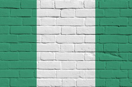 Nigeria flag depicted in paint colors on old brick wall close up. Textured banner on big brick wall masonry background 写真素材