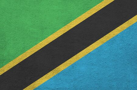 Tanzania flag depicted in bright paint colors on old relief plastering wall close up. Textured banner on rough background Stock fotó