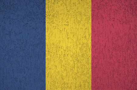 Chad flag depicted in bright paint colors on old relief plastering wall close up. Textured banner on rough background