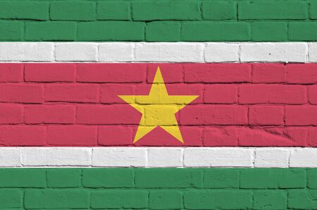 Suriname flag depicted in paint colors on old brick wall close up. Textured banner on big brick wall masonry background Stock fotó