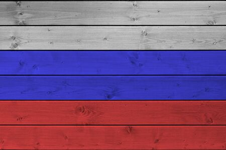 Russia flag depicted in bright paint colors on old wooden wall close up. Textured banner on rough background