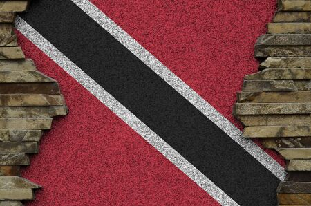 Trinidad and Tobago flag depicted in paint colors on old stone wall close up. Textured banner on rock wall background Stockfoto