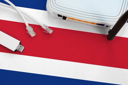 Costa Rica flag depicted on table with internet rj45 cable, wireless usb wifi adapter and router. Internet connection concept Stock fotó