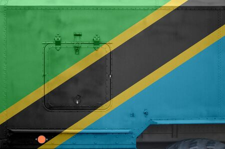 Tanzania flag depicted on side part of military armored truck close up. Army forces vehicle conceptual background Stock fotó