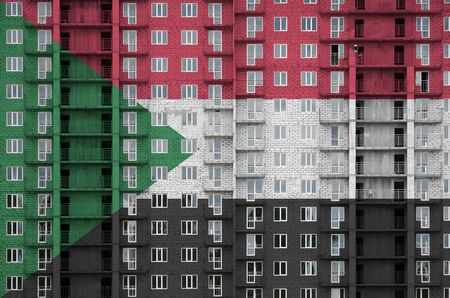 Sudan flag depicted in paint colors on multi-storey residental building under construction. Textured banner on big brick wall background