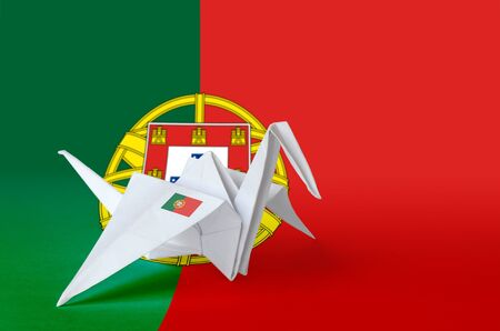 Portugal flag depicted on paper origami crane wing. Oriental handmade arts concept
