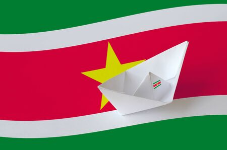 Suriname flag depicted on paper origami ship closeup. Oriental handmade arts concept