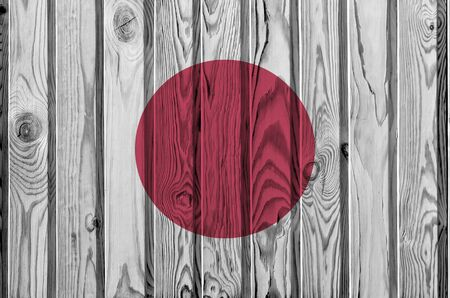Japan flag depicted in bright paint colors on old wooden wall close up. Textured banner on rough background