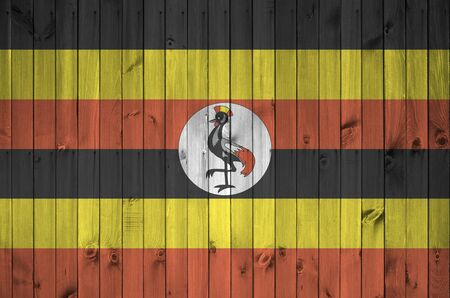 Uganda flag depicted in bright paint colors on old wooden wall close up. Textured banner on rough background