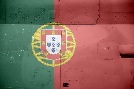 Portugal flag depicted on side part of military armored helicopter close up. Army forces aircraft conceptual background
