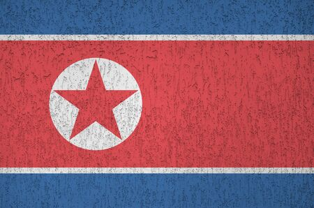 North Korea flag depicted in bright paint colors on old relief plastering wall close up. Textured banner on rough background