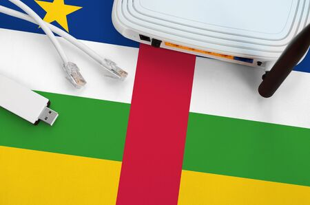 Central African Republic flag depicted on table with internet rj45 cable, wireless usb wifi adapter and router. Internet connection concept Фото со стока